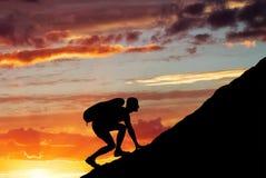 Σκιαγραφία ενός ατόμου που αναρριχείται στο βουνό Στοκ Φωτογραφίες