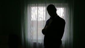 Σκιαγραφία ενός ατόμου που βάζει στο σακάκι του στο σκοτεινό δωμάτιο απόθεμα βίντεο