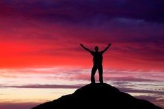 Σκιαγραφία ενός ατόμου σε μια κορυφή βουνών Στοκ εικόνα με δικαίωμα ελεύθερης χρήσης