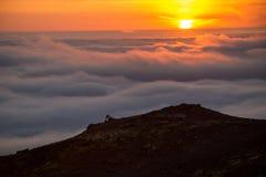 Σκιαγραφία ενός ατόμου στην κορυφογραμμή επάνω από τη θάλασσα των σύννεφων, misty βουνά στο ηλιοβασίλεμα στην Ισλανδία στοκ φωτογραφία με δικαίωμα ελεύθερης χρήσης