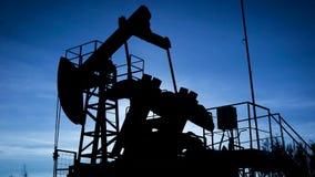 Σκιαγραφία ενός βιομηχανικού αντλώντας πετρελαίου γρύλων αντλιών πετρελαίου στον τομέα, επιχείρηση πετρελαίου απόθεμα βίντεο