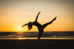 Σκιαγραφία ενός ευτυχούς κοριτσιού χορευτών που πηδά το ηλιοβασίλεμα Στοκ φωτογραφία με δικαίωμα ελεύθερης χρήσης