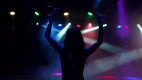 Σκιαγραφία ενός ευτυχούς χαλαρωμένου χορεύοντας κοριτσιού στο σκοτάδι απόθεμα βίντεο