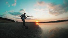 Σκιαγραφία ενός κιθαρίστα μουσικών ατόμων που παίζει μια ηλεκτρική κιθάρα στο ηλιοβασίλεμα κοντά στο νερό αρσενική έννοια κιθαρισ απόθεμα βίντεο