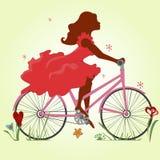 Σκιαγραφία ενός κοριτσιού σε ένα κόκκινο φόρεμα σε ένα ποδήλατο Στοκ Φωτογραφία