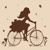 Σκιαγραφία ενός κοριτσιού σε ένα ποδήλατο στους καφετιούς τόνους Στοκ Εικόνες