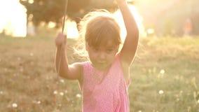 Σκιαγραφία ενός μικρού κοριτσιού στο πάρκο στο ηλιοβασίλεμα φιλμ μικρού μήκους