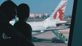 Σκιαγραφία ενός μικρών αγοριού και ενός πατέρα μπροστά από το τελικό παράθυρο που εξετάζει τα αεροπλάνα φιλμ μικρού μήκους