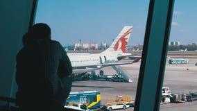 Σκιαγραφία ενός μικρών αγοριού και ενός πατέρα μπροστά από το τελικό παράθυρο που εξετάζει τα αεροπλάνα απόθεμα βίντεο