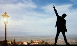 Σκιαγραφία ενός μόνιμου ατόμου με αυξημένος επάνω στα όπλα στην κορυφή στοκ εικόνα με δικαίωμα ελεύθερης χρήσης