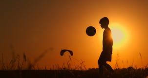 Σκιαγραφία ενός παίζοντας ποδοσφαίρου ή ενός ποδοσφαίρου αγοριών στην παραλία με την όμορφη παιδική ηλικία υποβάθρου ηλιοβασιλέμα απόθεμα βίντεο