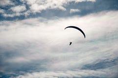 Σκιαγραφία ενός πετώντας ανεμόπτερου σε ένα κλίμα των σύννεφων Στοκ Εικόνες