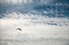 Σκιαγραφία ενός πετώντας ανεμόπτερου σε ένα κλίμα των σύννεφων Στοκ Φωτογραφία