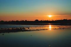 Σκιαγραφία ενός προσγειώνομαι-σταδίου και ενός ξύλου ως sunsets σε χαμηλότερο στοκ εικόνα με δικαίωμα ελεύθερης χρήσης