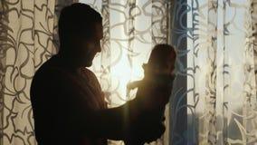 Σκιαγραφία ενός υγιούς νέου πατέρα που παίζει με το μωρό από το παράθυρο στο ηλιοβασίλεμα απόθεμα βίντεο