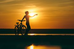 Σκιαγραφία ενός φίλαθλου κοριτσιού σε ένα κοστούμι που στέκεται κοντά σε ένα ποδήλατο στο νερό και τα σημεία το χέρι της στην από στοκ εικόνες