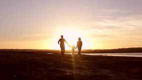 Σκιαγραφία, ευτυχές παιδί με τη μητέρα και πατέρας, οικογένεια στο ηλιοβασίλεμα, καλοκαίρι Τρέξιμο, που ανατρέφει το μωρό επάνω σ φιλμ μικρού μήκους
