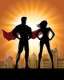 Σκιαγραφία ζεύγους Superhero με το υπόβαθρο οριζόντων πόλεων Στοκ Φωτογραφίες