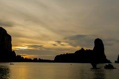 Σκιαγραφία ηλιοβασιλέματος των βράχων στον κόλπο θάλασσας Στοκ εικόνα με δικαίωμα ελεύθερης χρήσης