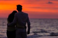 Σκιαγραφία ηλιοβασιλέματος του νέου ερωτευμένου αγκαλιάσματος ζευγών στην παραλία Στοκ Εικόνες