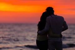 Σκιαγραφία ηλιοβασιλέματος του νέου ερωτευμένου αγκαλιάσματος ζευγών στην παραλία Στοκ Φωτογραφία