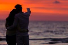 Σκιαγραφία ηλιοβασιλέματος του νέου ερωτευμένου αγκαλιάσματος ζευγών στην παραλία Στοκ φωτογραφίες με δικαίωμα ελεύθερης χρήσης