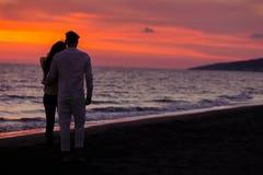 Σκιαγραφία ηλιοβασιλέματος του νέου ερωτευμένου αγκαλιάσματος ζευγών στην παραλία Στοκ φωτογραφία με δικαίωμα ελεύθερης χρήσης