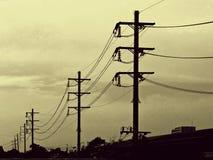 Σκιαγραφία, θέση ηλεκτρικής ενέργειας στο χρυσό ουρανό Στοκ Φωτογραφία
