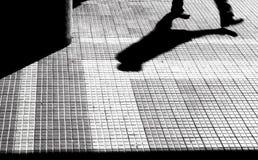 Σκιαγραφία και σκιά ενός περπατήματος προσώπων Στοκ Φωτογραφίες