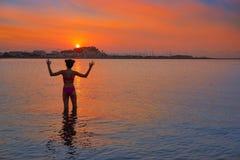 Σκιαγραφία κοριτσιών στις ανοικτές αγκάλες ηλιοβασιλέματος παραλιών στοκ εικόνα με δικαίωμα ελεύθερης χρήσης