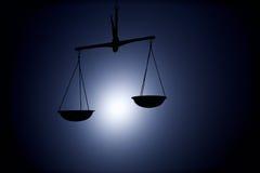 Σκιαγραφία κλίμακας δικαιοσύνης στο σκοτεινό υπόβαθρο στοκ εικόνες