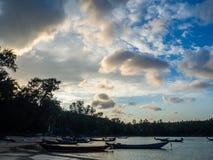 Σκιαγραφία μιας βάρκας και των φοινίκων ενάντια στον ήλιο ρύθμισης με τα σύννεφα στοκ εικόνες
