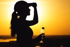 Σκιαγραφία μιας γυναίκας με το μπουκάλι μετά από τη σωματική άσκηση στη φύση, αθλητικό θηλυκό σχεδιάγραμμα στο ηλιοβασίλεμα, έννο Στοκ φωτογραφίες με δικαίωμα ελεύθερης χρήσης