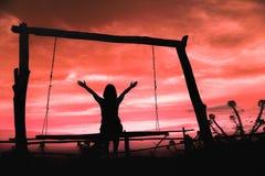 Σκιαγραφία μιας γυναίκας που έχει τη συνεδρίαση διασκέδασης στην ταλάντευση στο ηλιοβασίλεμα με τα όμορφα σύννεφα στο υπόβαθρο, τ στοκ φωτογραφίες
