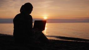 Σκιαγραφία μιας γυναίκας που εργάζεται με ένα lap-top θαλασσίως στο ηλιοβασίλεμα φιλμ μικρού μήκους