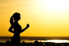 Σκιαγραφία μιας γυναίκας που στη φύση στο ηλιοβασίλεμα, το αθλητικό θηλυκό σχεδιάγραμμα, την έννοια του αθλητισμού, τον ελεύθερο  Στοκ Εικόνες