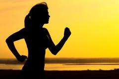 Σκιαγραφία μιας γυναίκας που στη φύση στο ηλιοβασίλεμα, το αθλητικό θηλυκό σχεδιάγραμμα, την έννοια του αθλητισμού, τον ελεύθερο  Στοκ Εικόνα