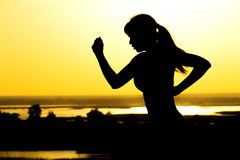 Σκιαγραφία μιας γυναίκας που στη φύση στο ηλιοβασίλεμα, το αθλητικό θηλυκό σχεδιάγραμμα, την έννοια του αθλητισμού, τον ελεύθερο  Στοκ φωτογραφία με δικαίωμα ελεύθερης χρήσης