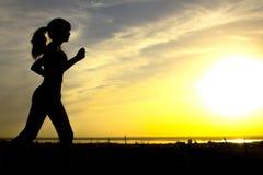 Σκιαγραφία μιας γυναίκας που στη φύση στο ηλιοβασίλεμα, το αθλητικό θηλυκό σχεδιάγραμμα, την έννοια του αθλητισμού, τον ελεύθερο  Στοκ Φωτογραφίες
