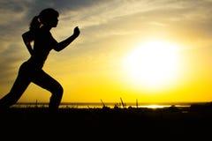 Σκιαγραφία μιας γυναίκας που στη φύση στο ηλιοβασίλεμα, το αθλητικό θηλυκό σχεδιάγραμμα, την έννοια του αθλητισμού, τον ελεύθερο  Στοκ εικόνα με δικαίωμα ελεύθερης χρήσης
