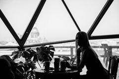 Σκιαγραφία μιας γυναίκας σε έναν καφέ με ένα φλιτζάνι του καφέ Στοκ φωτογραφία με δικαίωμα ελεύθερης χρήσης