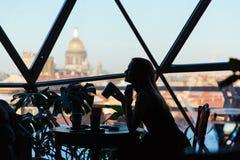 Σκιαγραφία μιας γυναίκας σε έναν καφέ με ένα φλιτζάνι του καφέ Στοκ Φωτογραφίες