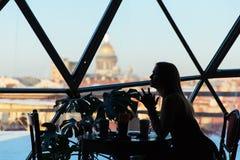 Σκιαγραφία μιας γυναίκας σε έναν καφέ με ένα φλιτζάνι του καφέ Στοκ Εικόνες