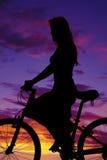 Σκιαγραφία μιας γυναίκας σε ένα ποδήλατο επάνω στενό στοκ εικόνα