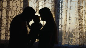 Σκιαγραφία μιας ευτυχούς οικογένειας Είναι το σπίτι από το παράθυρο στο ηλιοβασίλεμα, ήπια λαβή το παιδί στα όπλα σας φιλμ μικρού μήκους