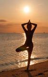 Σκιαγραφία μιας νέας γιόγκας άσκησης γυναικών στην παραλία στο ηλιοβασίλεμα στοκ εικόνες με δικαίωμα ελεύθερης χρήσης