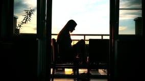 Σκιαγραφία μιας νέας γυναίκας που μιλά στο κινητό τηλέφωνό της στο σπίτι φιλμ μικρού μήκους