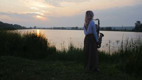 Σκιαγραφία μιας νέας γυναίκας που παίζει στο saxophone κοντά στο riverbank στην αυγή, ένα όμορφο κορίτσι σε ένα μακρύ φόρεμα με έ φιλμ μικρού μήκους