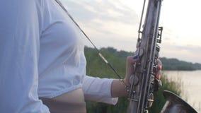 Σκιαγραφία μιας νέας γυναίκας που παίζει στο saxophone κοντά στο riverbank στην αυγή, ένα όμορφο κορίτσι σε ένα μακρύ φόρεμα με έ απόθεμα βίντεο
