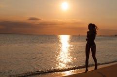 Σκιαγραφία μιας νέας γυναίκας που τρέχει στην παραλία στο ηλιοβασίλεμα στοκ φωτογραφία με δικαίωμα ελεύθερης χρήσης